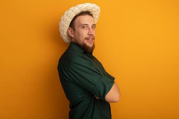 ビーチ帽子をかぶった幸せなハンサムなブロンドの男は、オレンジ色の壁に分離された腕を組んで横に立っています