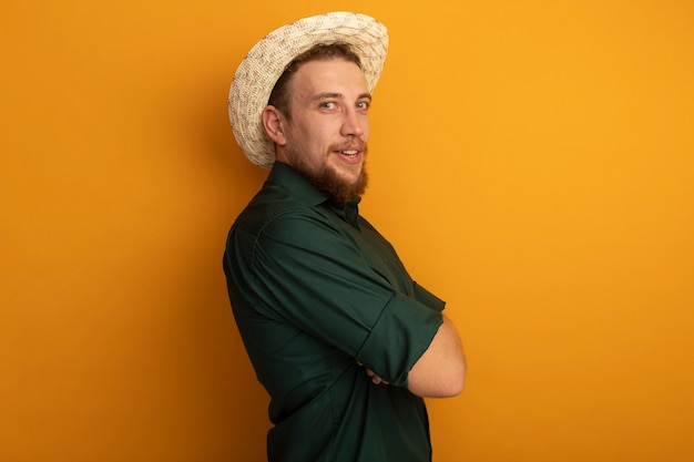 Soddisfatto bell'uomo biondo con cappello da spiaggia si leva in piedi lateralmente con le braccia incrociate isolato sulla parete arancione