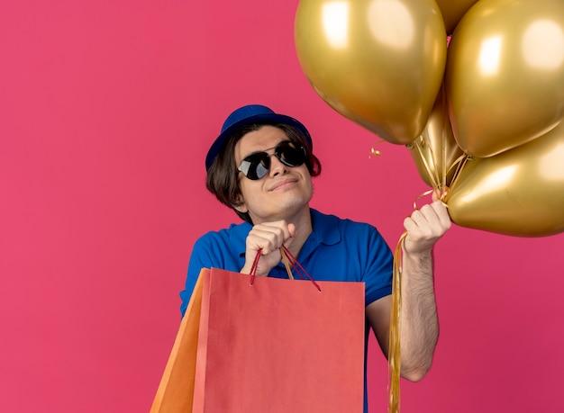 파란색 파티 모자를 쓰고 태양 안경에 기쁘게 잘 생긴 백인 남자가 헬륨 풍선과 종이 쇼핑백을 보유하고 있습니다.