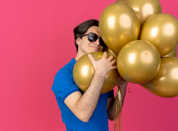 L'uomo caucasico bello e contento in occhiali da sole tiene palloncini di elio