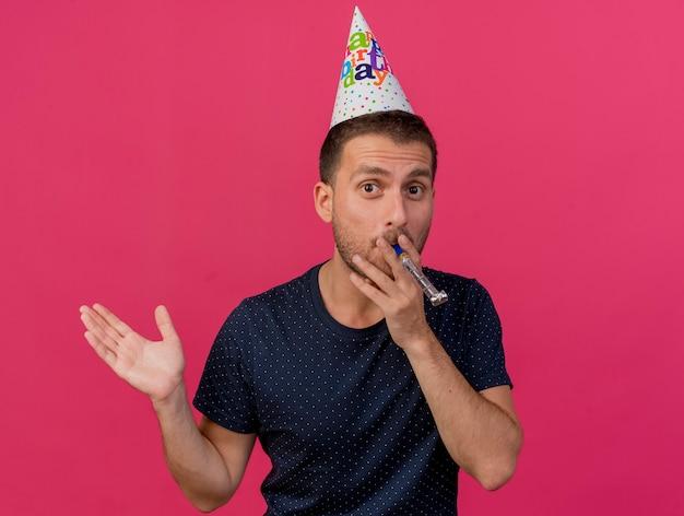 コピースペースでピンクの背景に分離された笛を吹く誕生日キャップを身に着けているハンサムな白人男性