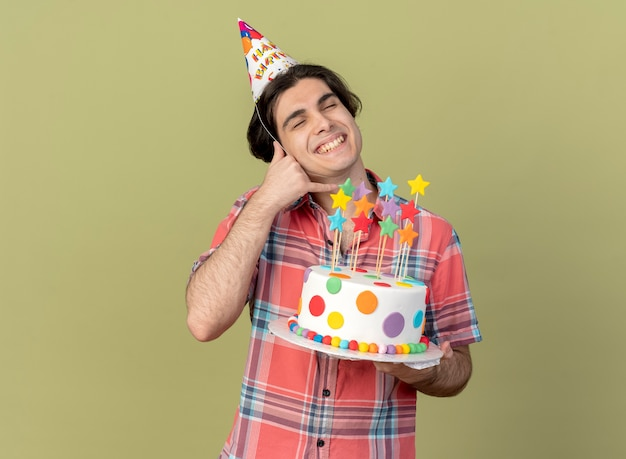 Pleased handsome caucasian man wearing birthday cap holds birthday cake and gestures call me sign