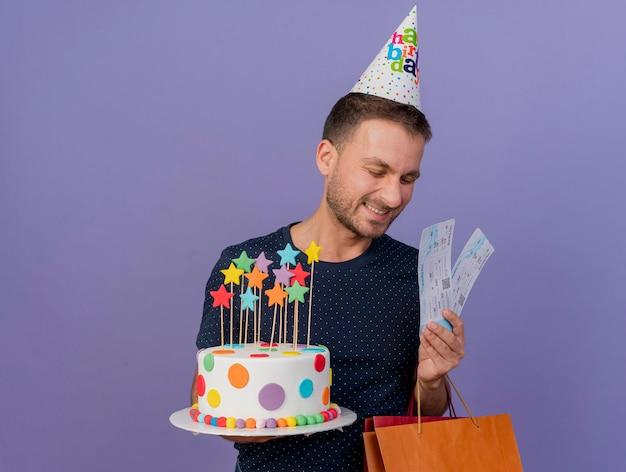 생일 모자를 쓰고 기쁘게 잘 생긴 백인 남자는 생일 케이크 종이 쇼핑백 선물 상자와 복사 공간이 보라색 배경에 고립 된 항공 티켓을 보유하고 있습니다.