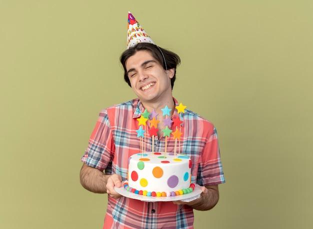 誕生日の帽子をかぶった満足しているハンサムな白人男性が誕生日ケーキを持っている