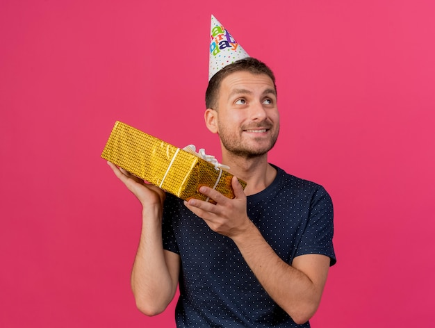 誕生日のキャップを身に着けている幸せなハンサムな白人男性は、コピースペースでピンクの背景に分離された側を見てギフトボックスを保持します