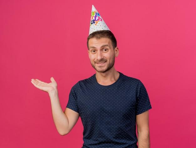 誕生日のキャップを身に着けている幸せなハンサムな白人男性は、コピースペースでピンクの背景に分離された手を開いたままにします。