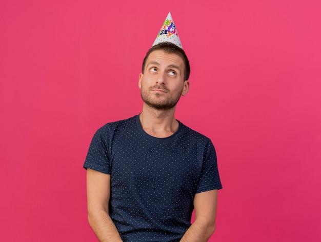 誕生日の帽子をかぶって幸せなハンサムな白人男性は、コピースペースでピンクの背景に分離された側を見て