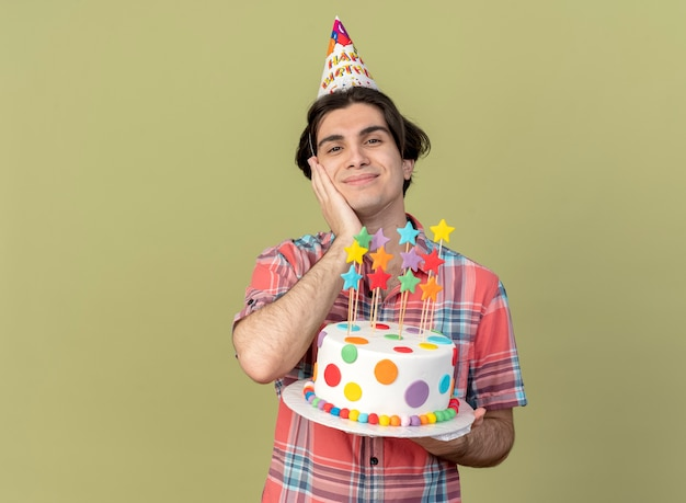 Pleased handsome caucasian man wearing birthday cap puts hand on face and holds birthday cake