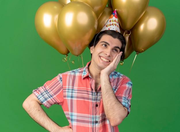 생일 모자를 쓰고 기쁘게 잘 생긴 백인 남자가 헬륨 풍선 앞에 서서 얼굴에 손을 댔다.