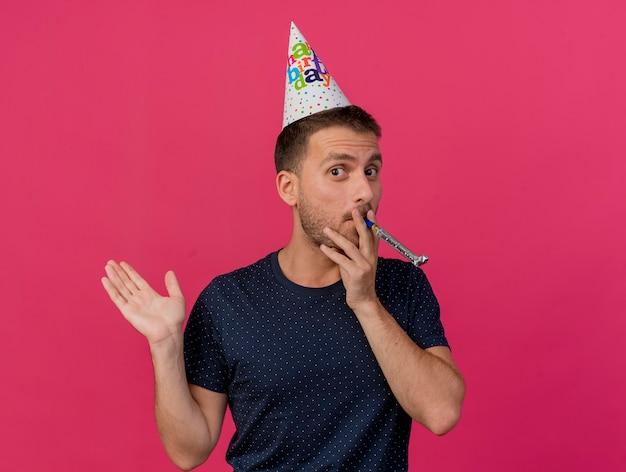 コピースペースでピンクの背景に分離されたホイッスルを吹く上げられた手で誕生日キャップスタンドを身に着けている幸せなハンサムな白人男性
