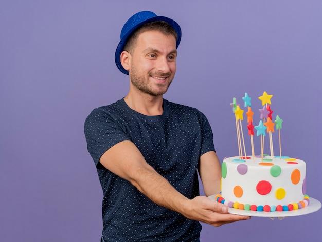 Felice uomo caucasico bello che indossa cappello blu tiene e guarda la torta di compleanno isolata su sfondo viola con spazio di copia