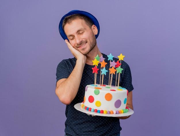 Soddisfatto bell'uomo caucasico che indossa il cappello blu mette la mano sul viso e tiene la torta di compleanno isolata su sfondo viola con spazio di copia