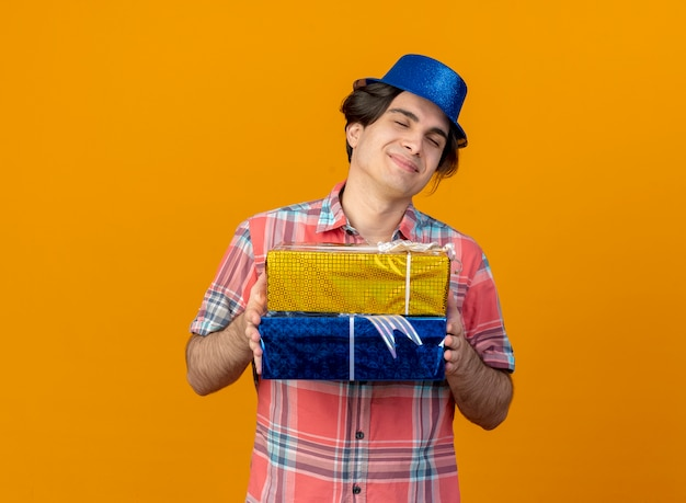 파란색 파티 모자를 쓰고 기쁘게 잘 생긴 백인 남자는 선물 상자를 보유하고