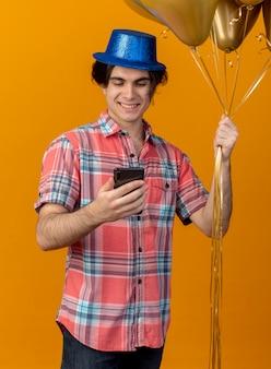 파란색 파티 모자를 쓰고 기쁘게 잘 생긴 백인 남자는 헬륨 풍선을 보유하고 전화를 찾습니다