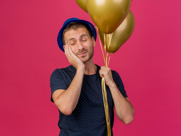 Il bello uomo caucasico bello che porta il cappello blu del partito tiene i palloni dell'elio mette la mano sulla faccia isolata su fondo rosa con lo spazio della copia