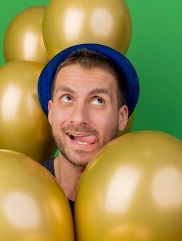 파란색 파티 모자를 쓰고 기쁘게 잘 생긴 백인 남자가 혀를 찌르고 복사 공간이 녹색 배경에 고립 된 찾고 헬륨 풍선을 보유하고 있습니다.