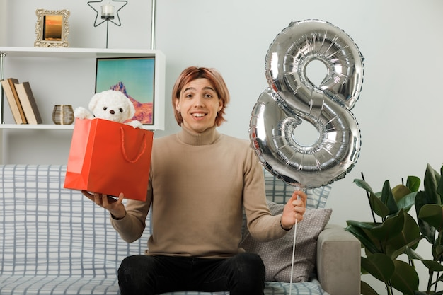 Pleased handsome guy on happy women day holding number eight balloon with gift bag sitting on sofa in living room