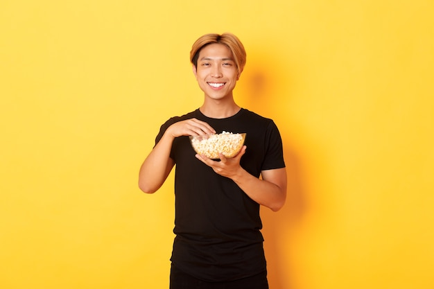 Pleased handsome korean guy smiling happy as enjoying watching movie or tv series, eating popcorn, standing yellow wall.