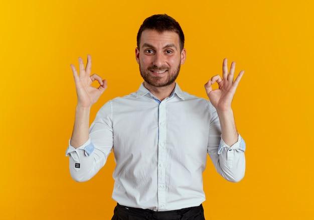 Довольный красавец жестикулирует знак рукой с двумя руками, изолированными на оранжевой стене