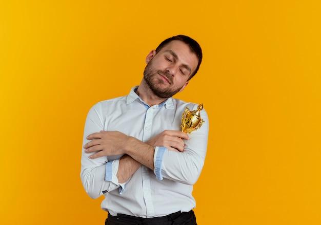 喜んでハンサムな男は、オレンジ色の壁に分離された勝者カップを保持し、抱擁します