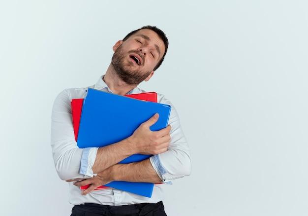 喜んでハンサムな男は白い壁に隔離されたファイルフォルダを保持します