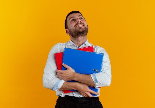 満足しているハンサムな男は、オレンジ色の壁に孤立して見上げるファイルフォルダを保持