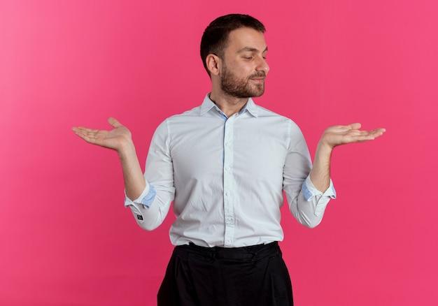 L'uomo bello soddisfatto tiene le mani aperte isolate sulla parete rosa