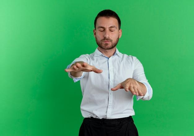Lieto bell'uomo tiene le mani dritte con gli occhi chiusi meditando isolato sulla parete verde