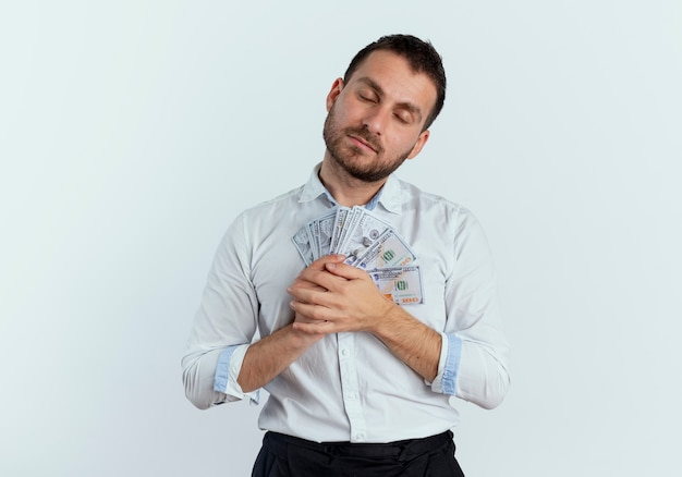 Pleased handsome man holds money with closed eyes isolated on white wall