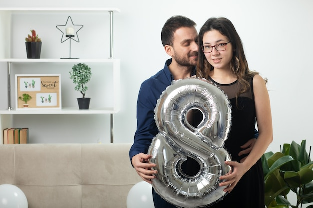 3월 국제 여성의 날에 거실에 서 있는 풍선 모양의 8개를 들고 안경을 쓴 예쁜 젊은 여성을 껴안고 기뻐하는 잘생긴 남자