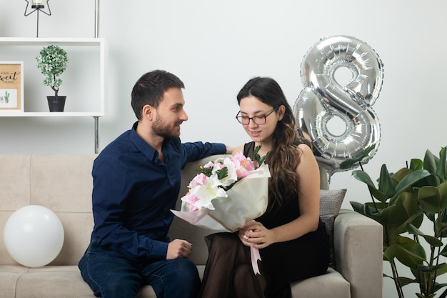 Pleased handsome man looking at pretty young woman in glasses holding bouquet of flowers sitting on couch in living room on march international women's day