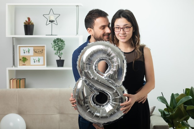 Pleased handsome man looking at pretty young woman in optical glasses holding balloon shaped eight standing in living room on march international women's day