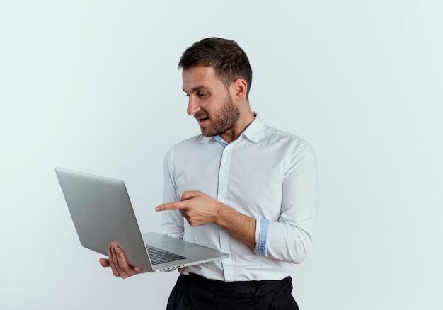 Довольный красавец смотрит и указывает на ноутбук, изолированный на белой стене