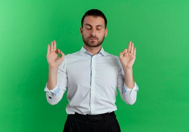 Piacevole bell'uomo finge di meditare con gli occhi chiusi isolati sulla parete verde