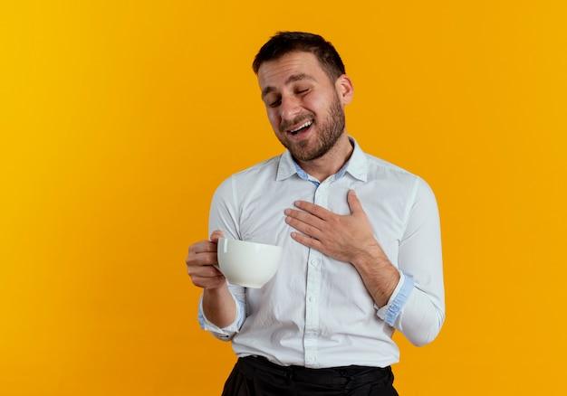 L'uomo bello soddisfatto mette la mano sulla tazza della tenuta del petto isolata sulla parete arancio