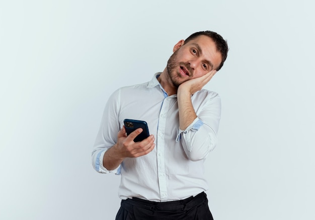 기쁘게 잘 생긴 남자가 흰 벽에 고립 된 전화를 들고 얼굴에 손을 넣습니다.