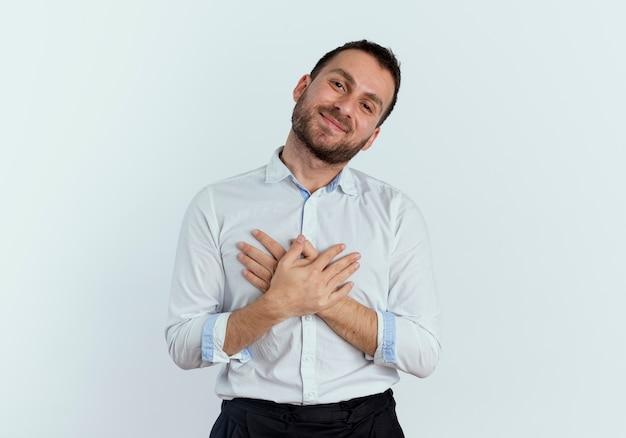 L'uomo bello soddisfatto mette le mani sul petto isolato sul muro bianco