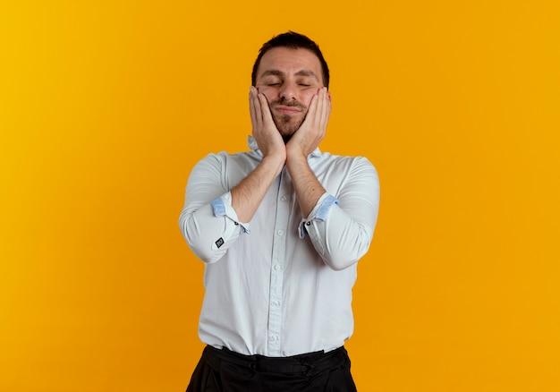 기쁘게 잘 생긴 남자는 오렌지 벽에 고립 된 얼굴에 손을 넣습니다.