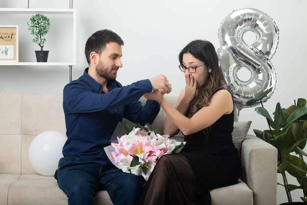 Pleased handsome man putting bracelet on hand of excited pretty young woman in optical glasses holding bouquet of flowers sitting on couch in living room on march international women's day
