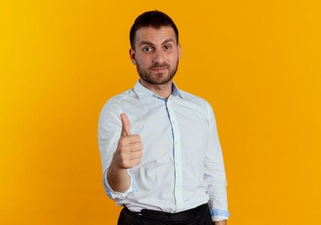 満足しているハンサムな男はオレンジ色の壁に孤立して親指を立てる