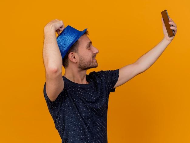 青いパーティーハットを身に着けて保持している幸せなハンサムな男は、コピースペースでオレンジ色の壁に分離された電話を見て自分撮りを取っている横に立っています