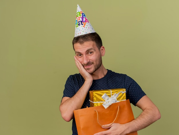 Pleased handsome man wearing birthday cap puts hand on face and holds gift box in paper shopping bag isolated on olive green wall with copy space