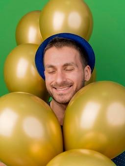 파란색 파티 모자를 쓰고 기쁘게 잘 생긴 남자는 복사 공간이 녹색 벽에 고립 된 헬륨 풍선과 함께 의미합니다