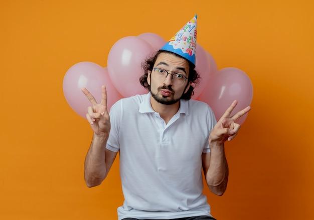 眼鏡と誕生日の帽子を身に着けているハンサムな男が前の風船に立って、オレンジ色の背景に分離された平和のジェスチャーを示して喜んで