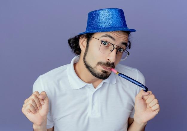 안경과 파란색 모자를 쓰고 휘파람을 불고 예 제스처를 보여주는 기쁘게 잘 생긴 남자