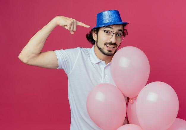 ピンクの背景で隔離の側に風船とポイントを保持している眼鏡と青い帽子を身に着けているハンサムな男を喜ばせる