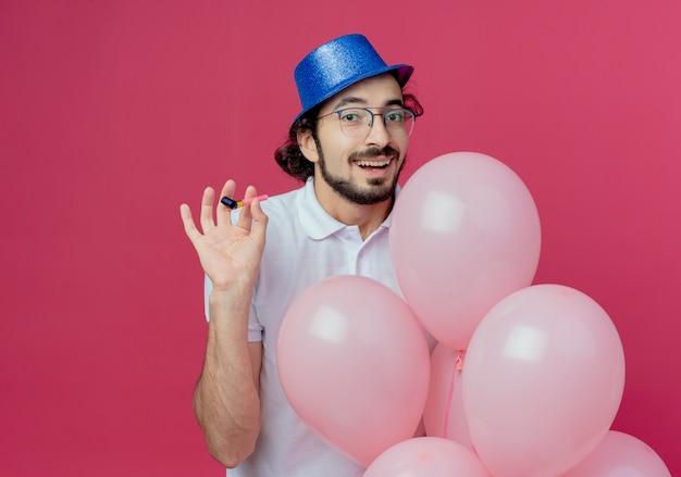 ピンクの背景に分離された風船と笛を保持している眼鏡と青い帽子を身に着けているハンサムな男を喜ばせる