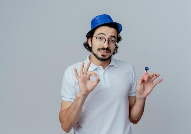 Soddisfatto bell'uomo con gli occhiali e cappello blu che tiene fischio e che mostra okey gesto isolato su sfondo bianco