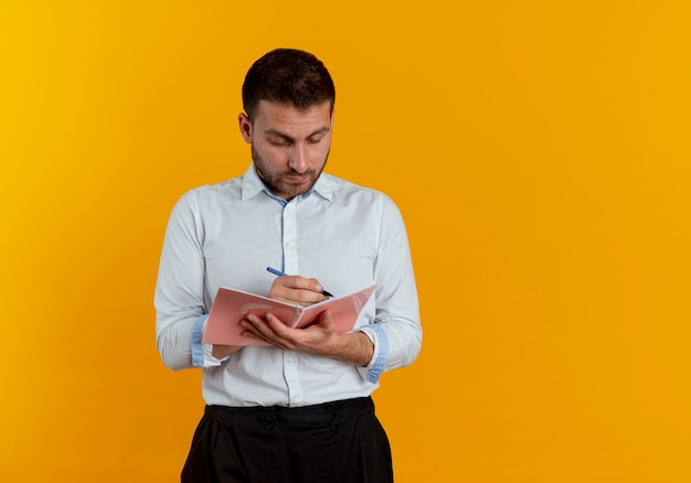 Pleased handsome man writes with pen in notebook isolated on orange wall