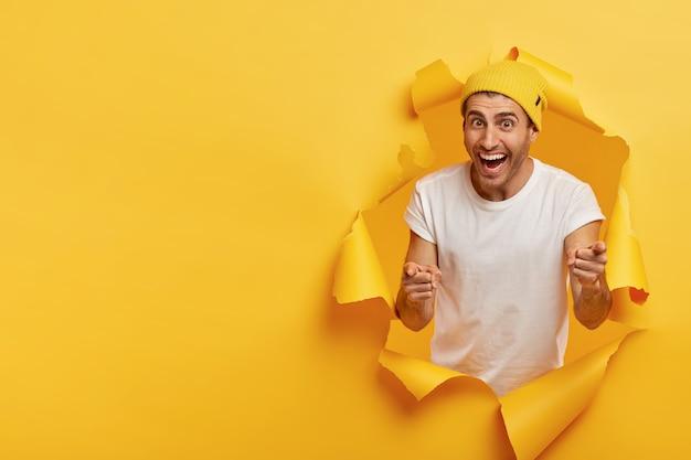 満足しているハンサムな若い男があなたを指さし、カメラに前指を向け、白いtシャツ、黄色の帽子をかぶって、紙の穴に立っています